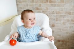 Cute child little girl eating healthy food in kindergarten. baby in chair stock photo