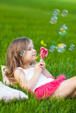 Cute child with lollipop resting on the grass Royalty Free Stock Images