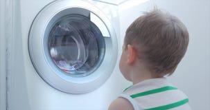 Cute Child Looks Inside the Washing Machine. Cylinder Spinning Machine. Concept Laundry Washing Machine, Industry stock footage