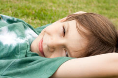 Cute child lying on the grass. Portrait of a smiling cute boy lying on the grass Stock Photo