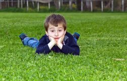 Cute child lying on grass Royalty Free Stock Images