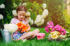 Cute child making flower bouquet in sunny summer garden Royalty Free Stock Photography