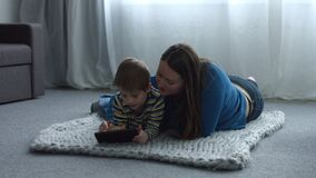 Cute child and mom with tablet pc relaxing at home. Cute little son and his beautiful mother with digital tablet relaxing at home while lying on floor in stock footage