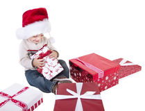 Cute Child Opening Christmas Presents. A cute little boy opening christmas presents and laughing in excitement. Isolated on a white background Stock Photo