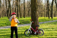 Cute child out cycling drinking bottled water. Cute little boy out cycling with his bike in a wooded park standing drinking bottled water with his bicycle Stock Photo