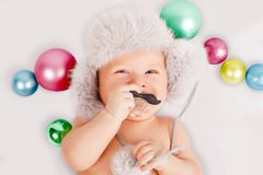 Cute child with a pacifier in the form of a mustache holding in his hand lies on his back next to Christmas toys. Smiling. Closeup Stock Images