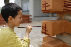 Cute child painting on building surface Stock Photo