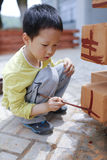 Cute child painting on building surface Stock Images