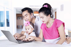 Cute child and parents looking at laptop Royalty Free Stock Photos