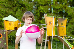 Cute child with pink ball on colorful playground. Cute child playing with a pink ball on a colorful playground Stock Image