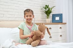 Cute child playing doctor with stuffed toy in hospital ward royalty free stock photo