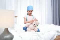 Cute child playing doctor with stuffed toy in hospital ward stock photo