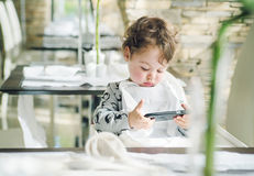 Cute child playing games on with a smartphone Royalty Free Stock Image