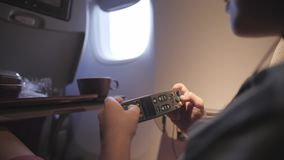 Cute child playing games, watching movie traveling by airplane.