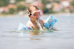Cute child playing in the ocean Stock Images