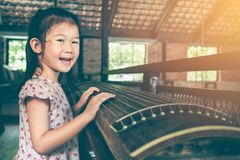 Cute child playing stringed instruments and having fun. Stock Photo