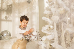 Cute child plays with a big glass toy on a bed near the Christmas tree Royalty Free Stock Photo