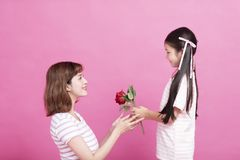 Cute child presenting red rose to mother royalty free stock photography