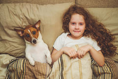 Cute child and puppy under quilt. Stock Photo
