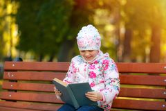 A cute child is reading a book in the park. stock photo