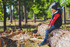 Cute child resting in nature. Carefree boy is sitting on falling tree in forest. He is smiling Royalty Free Stock Photos