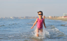 Cute child running in the waves at seaside Stock Images
