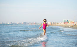 Cute child running in the waves at seaside Royalty Free Stock Photo