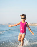 Cute child running in the waves at seaside Royalty Free Stock Photos