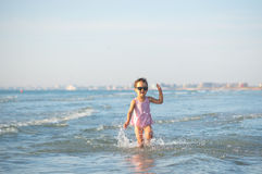 Cute child running in the waves Royalty Free Stock Image