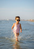 Cute child running in the waves Royalty Free Stock Photo