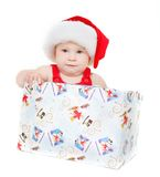 Cute child in santa hat sitting in gift box Royalty Free Stock Images