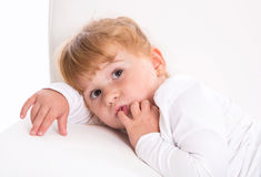 Cute child - shy girl lying on white sofa sucking thumb or finge Stock Photos