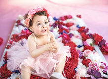 Cute child sitting on a bunch of flowers Royalty Free Stock Photo