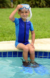 Cute child sitting on edge of swimming pool Stock Photo