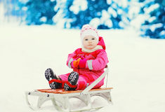 Cute child sitting with sled on snow in winter Stock Photos