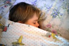 Cute child sleeps under blanket Royalty Free Stock Images