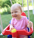 Cute child smiling in swing. Young cute child smiling in swing royalty free stock images