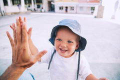 Cute child son giving high five to father. Cute boy son giving high five to father. Happy smiling portrait of child, outside. Close-up of adorable kid enjoying stock photos