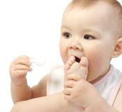Cute child with spoon sucks his foot Royalty Free Stock Image
