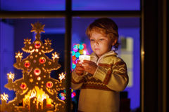 Cute child standing by window at Christmas time and holding cand Stock Image