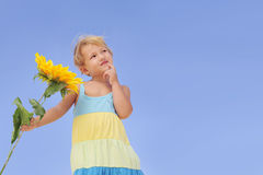 Cute child with sunflower looking at copy space Royalty Free Stock Images