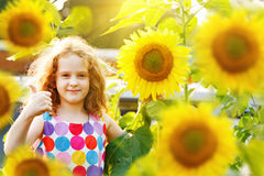 Cute child with sunflower, showing thumbs up. Stock Photography
