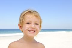 Cute child with sunscreen  at the beach. Cute child sunbathing with sunscreen in her face at the beach smiling Royalty Free Stock Photo