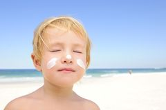 Cute child with sunscreen  at the beach. Cute child sunbathing with sunscreen in her face at the beach smiling Royalty Free Stock Photos
