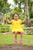 Cute Child on a Swing. Cute Asian child playing on a swing wearing nice yellow dress royalty free stock photography