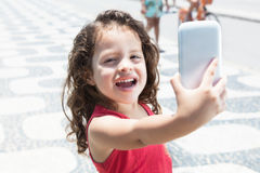Cute child taking photo with mobile phone Royalty Free Stock Image