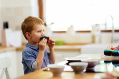 Cute child tasting cookies. In kitchen Royalty Free Stock Image