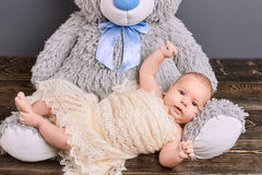 Cute child and teddy bear. Infant boy wrapped in shawl. Effective methods of upbringing Stock Photography