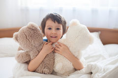 Cute child with teddy bears, lying in bed, looking at camera Stock Photo