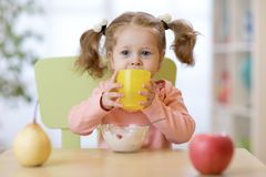 Cute child girl holding glass of water at home royalty free stock photography